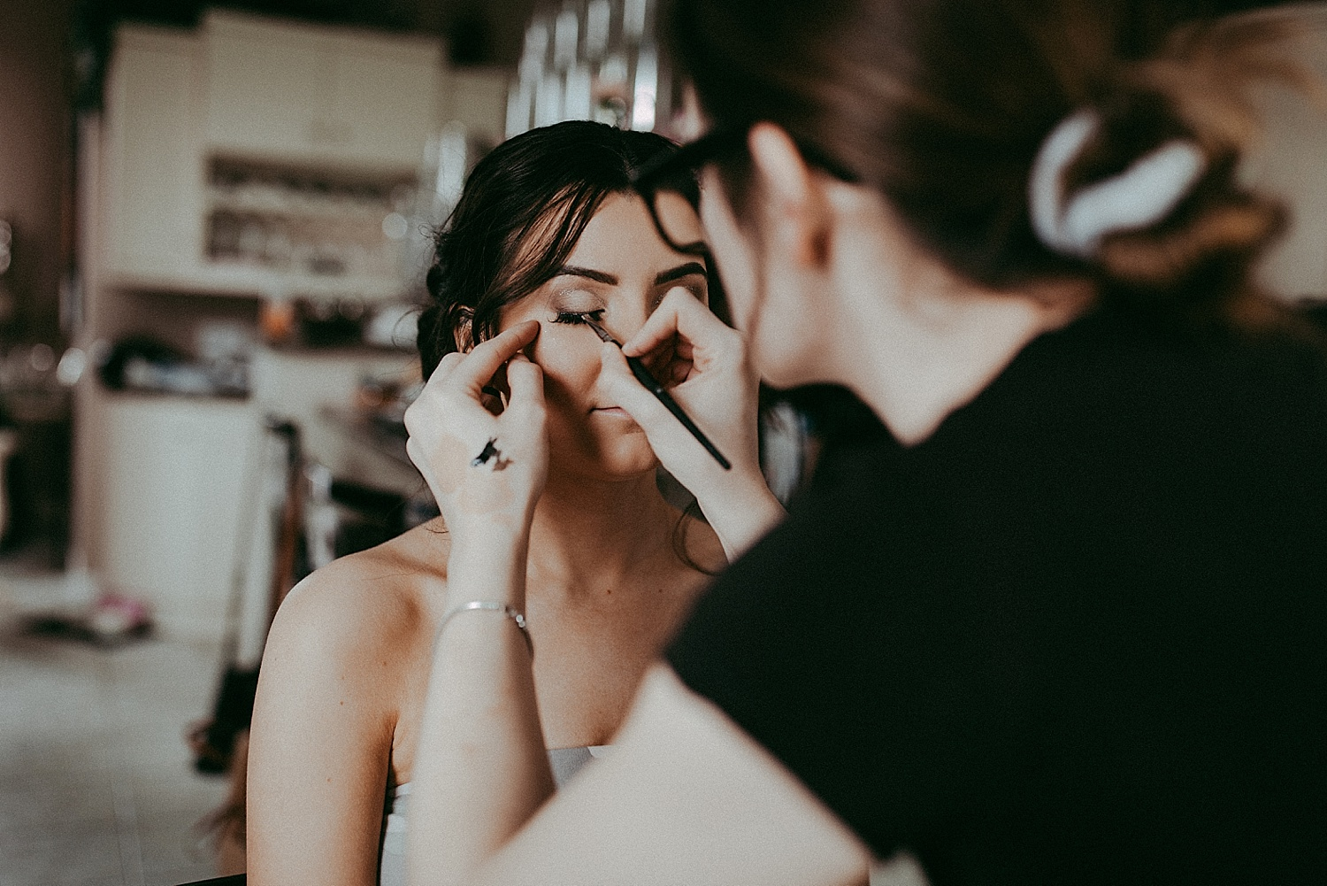 bride getting makeup done wedding photography