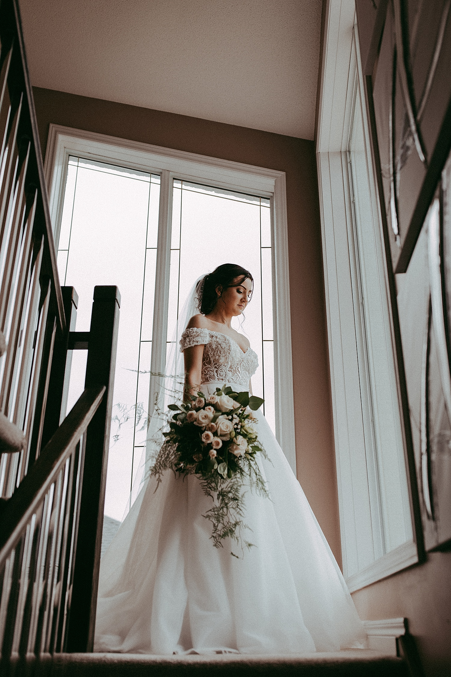 bride standing by window wedding photography
