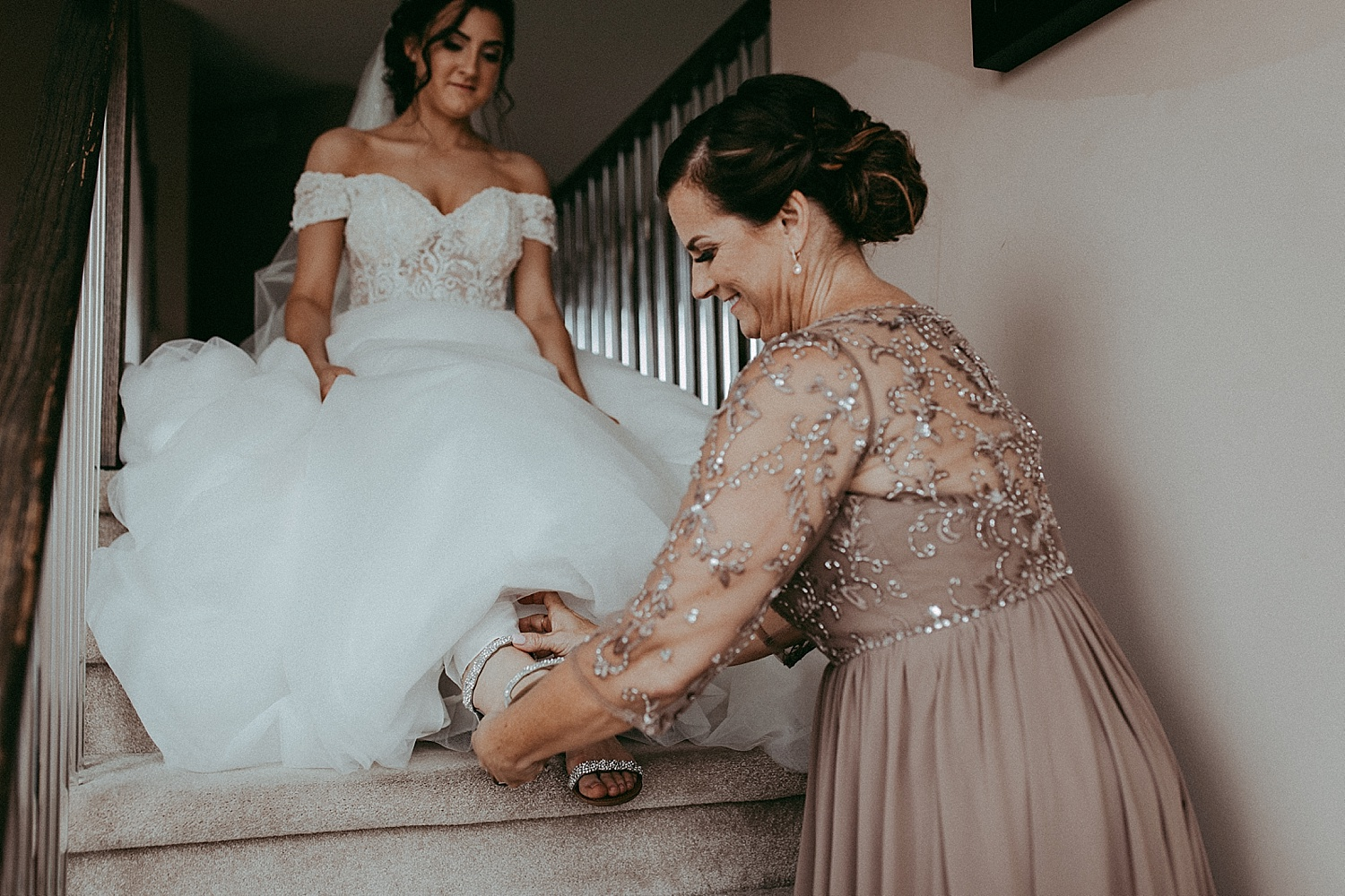 bridesmaid helping bride put on shoes wedding photography