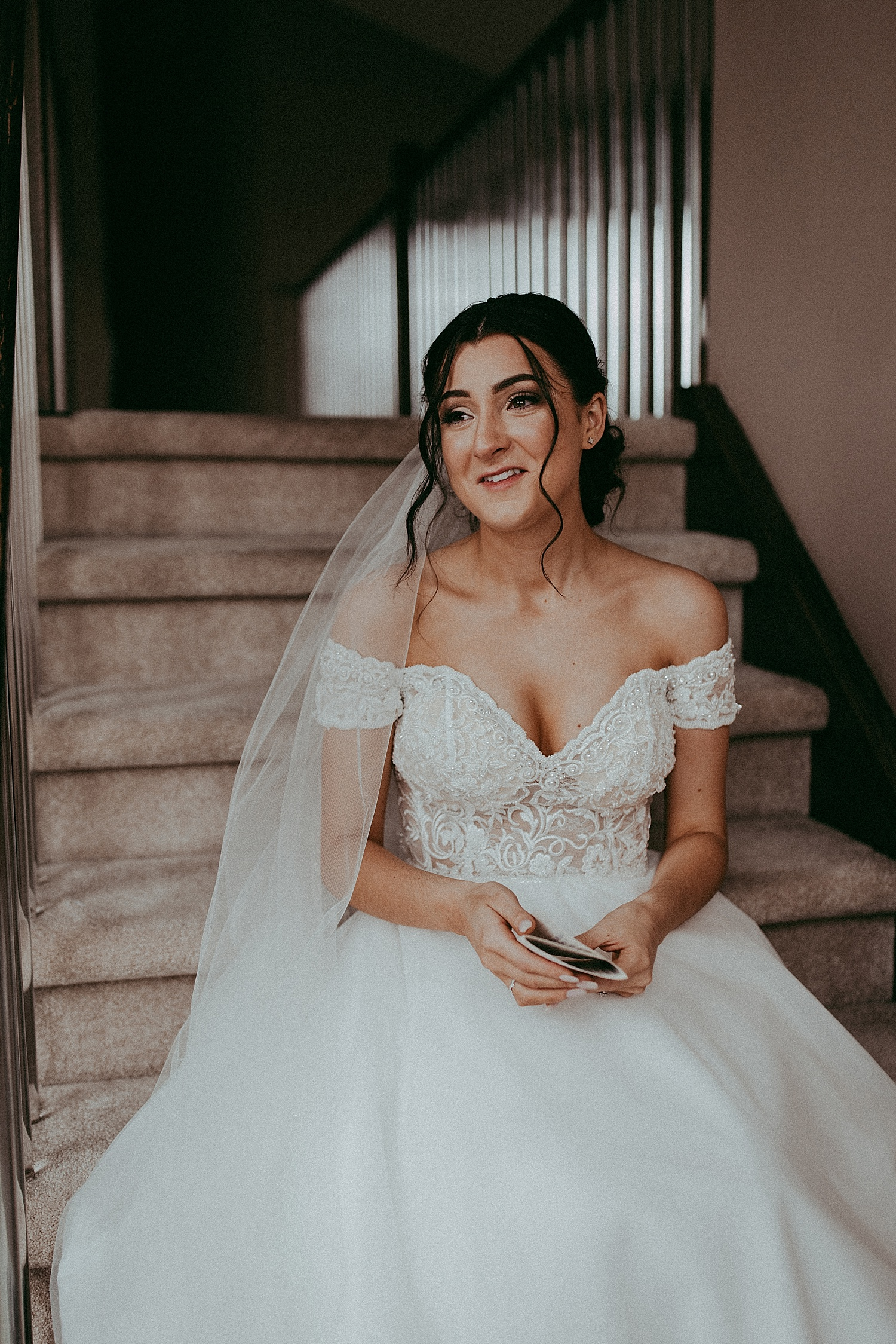 bride sitting on stairs smiling wedding photography