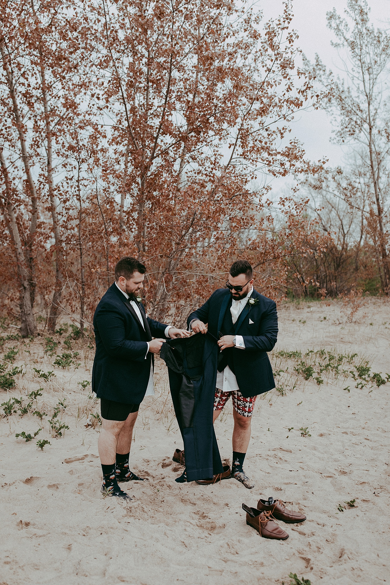 groom and groomsman holding a pair of pants, wedding photography
