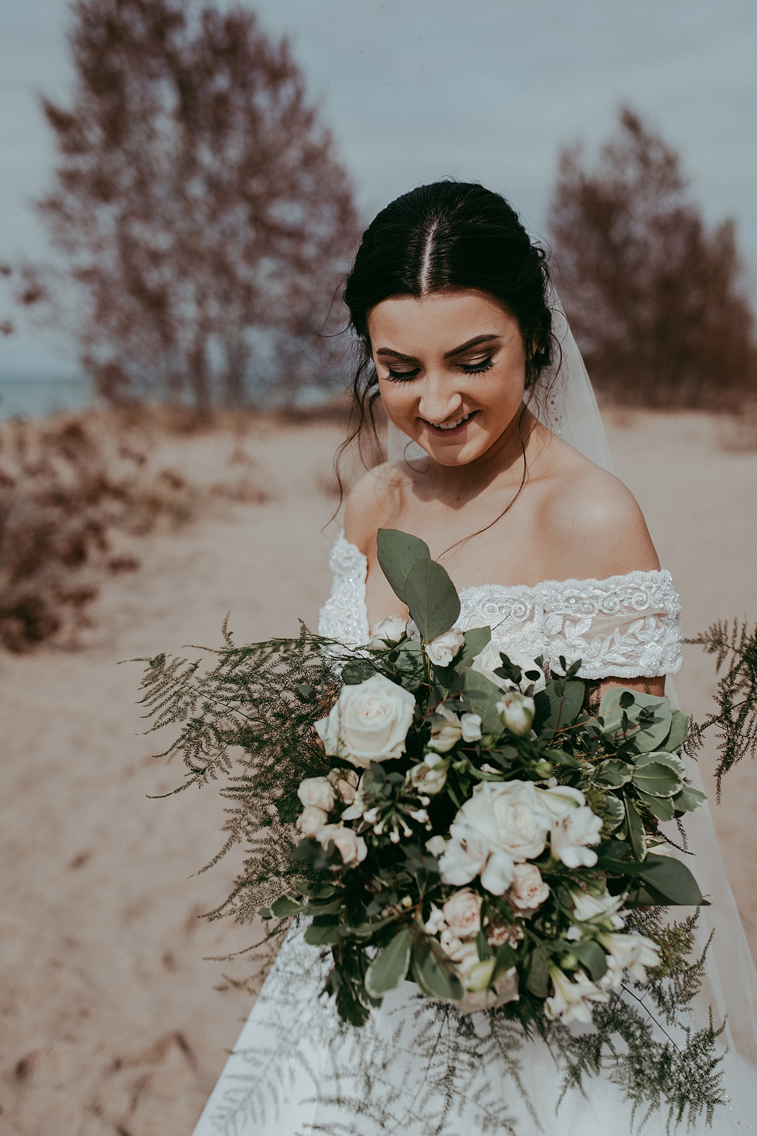 bride looking at her bouquet, wedding photography