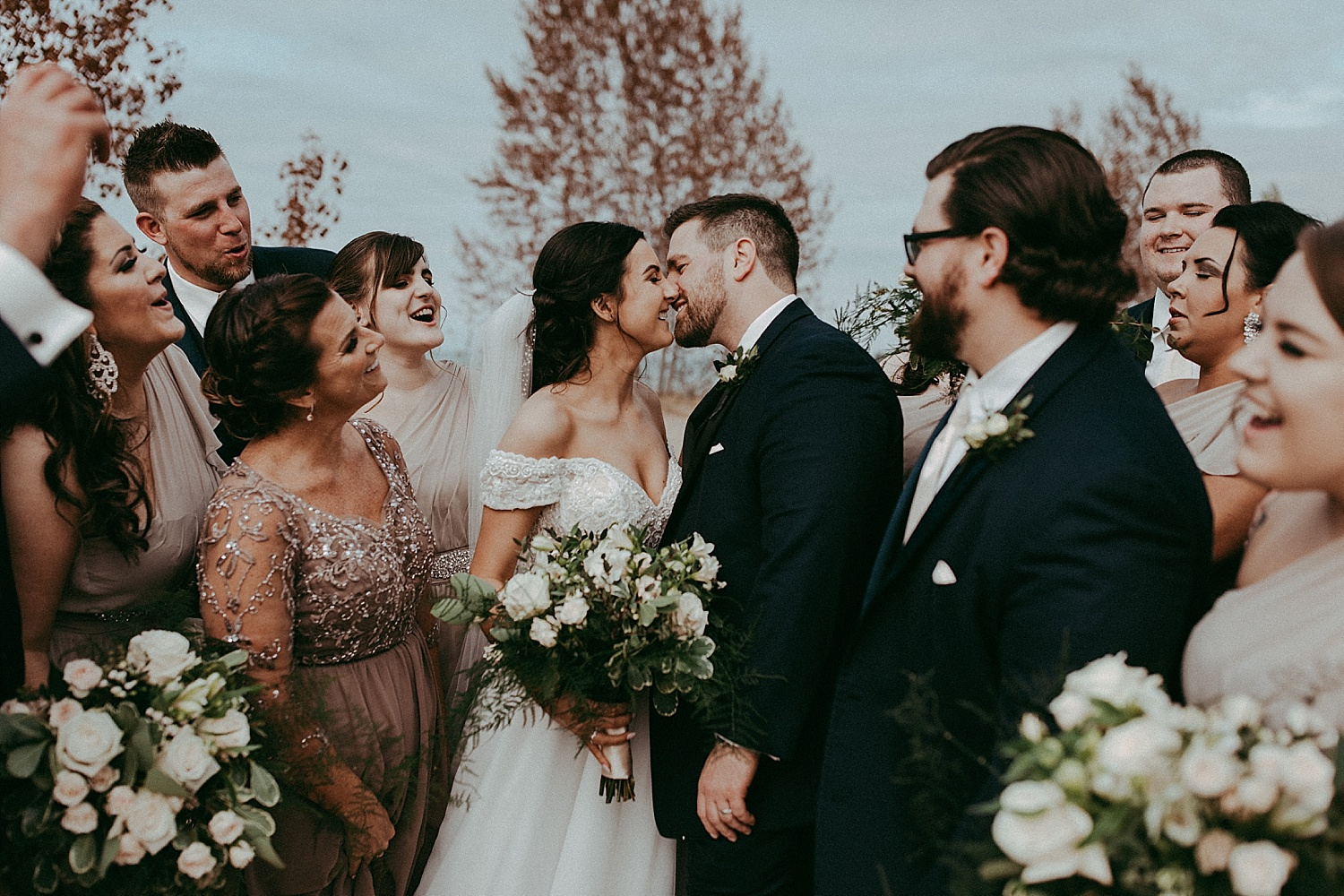 bride and groom kissing surrounded by the wedding party, wedding photography