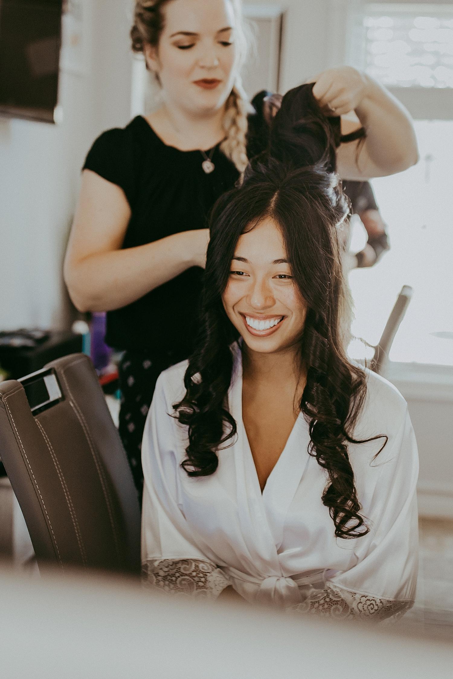 Bride having hair styled