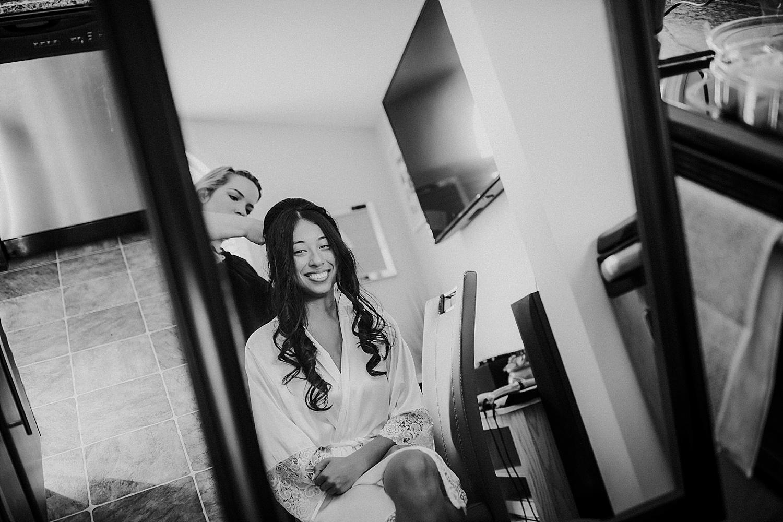 Bride looking in mirror having hair styled