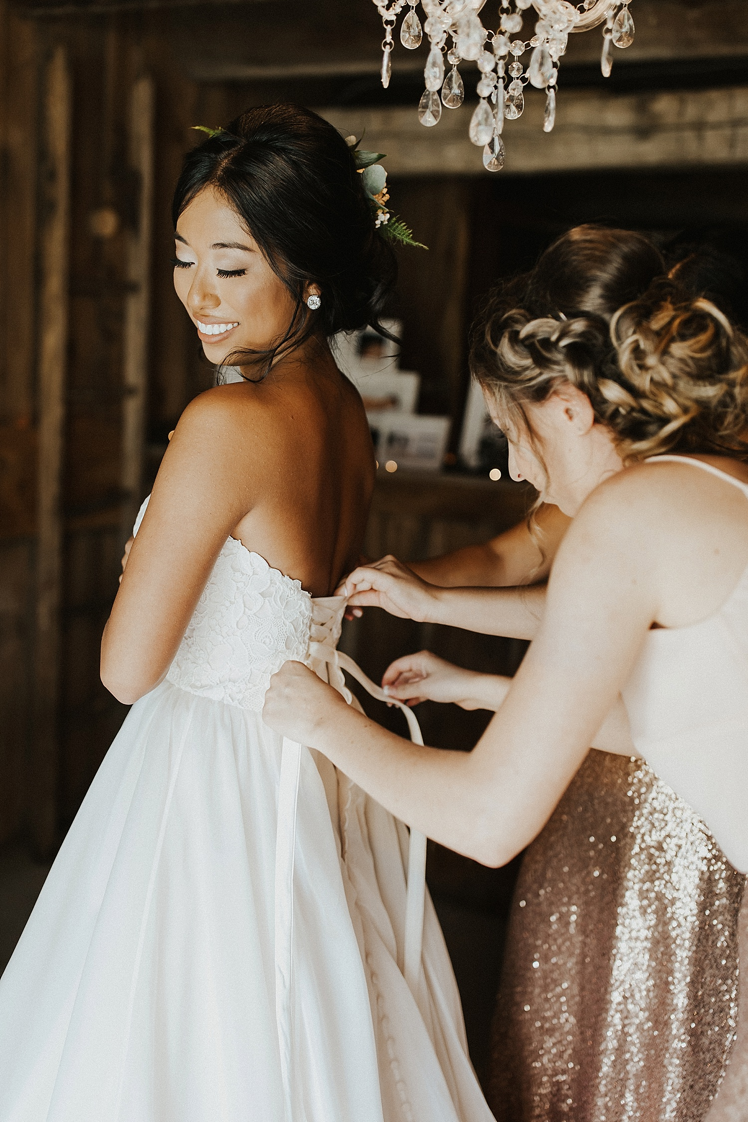 Bridesmaid helping the bride fasten her dress