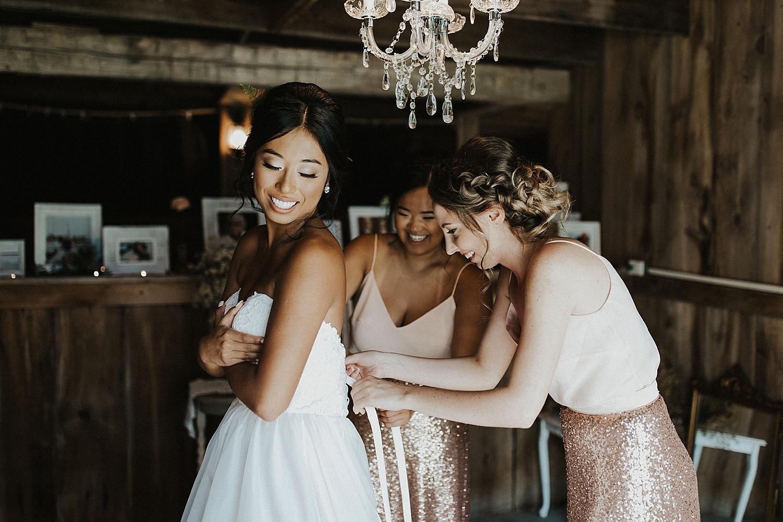 Bridesmaids helping the bride fasten her dress