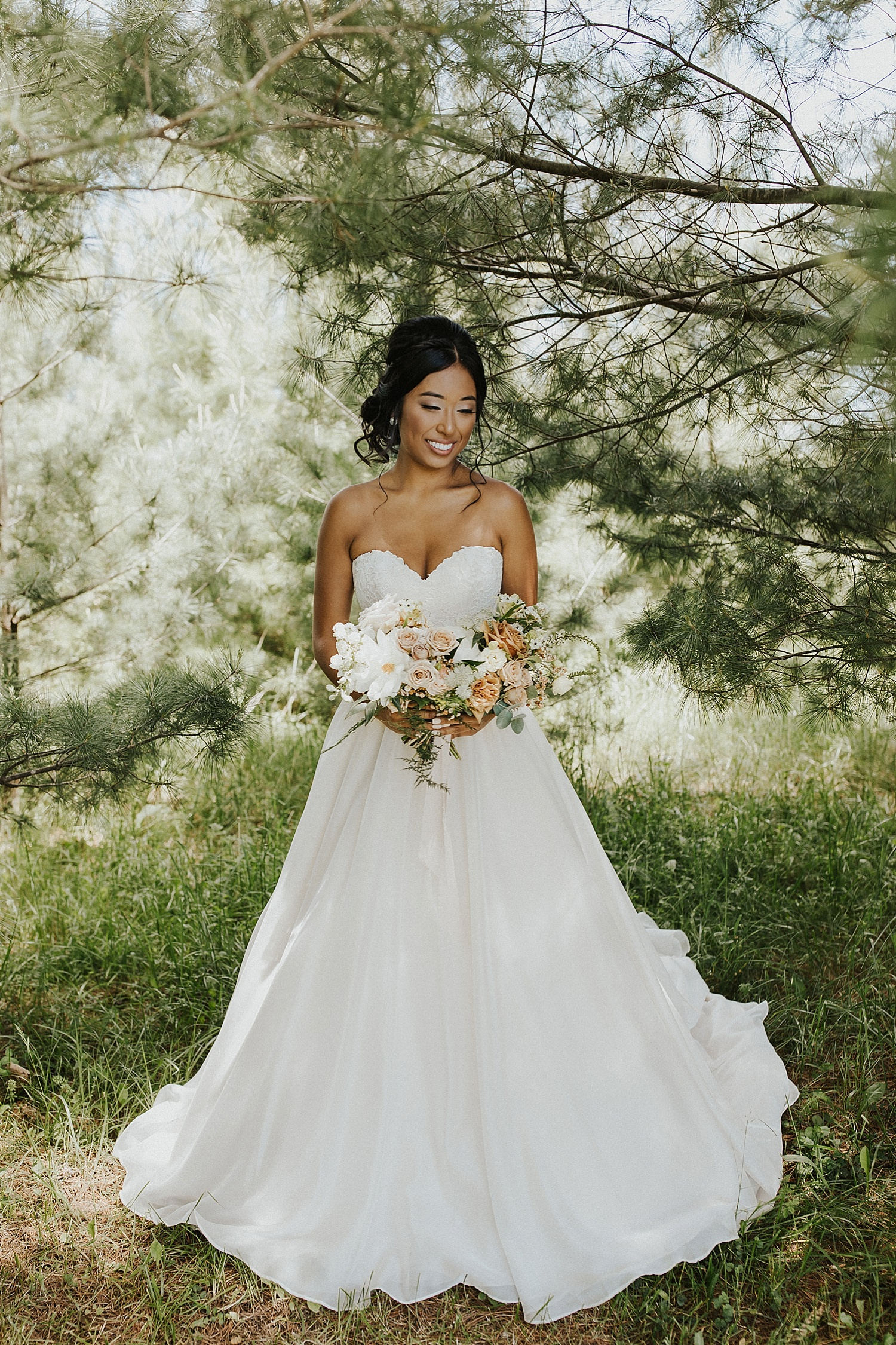 Bride standing among the trees, holding her bouquet