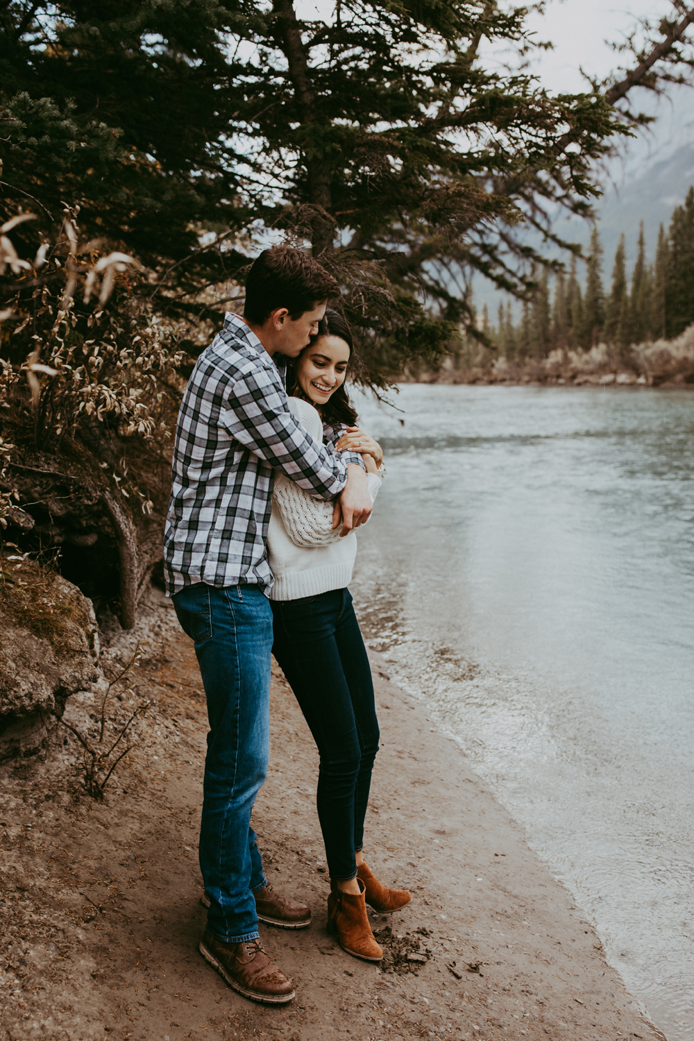 Engagement photography couple standing by a river